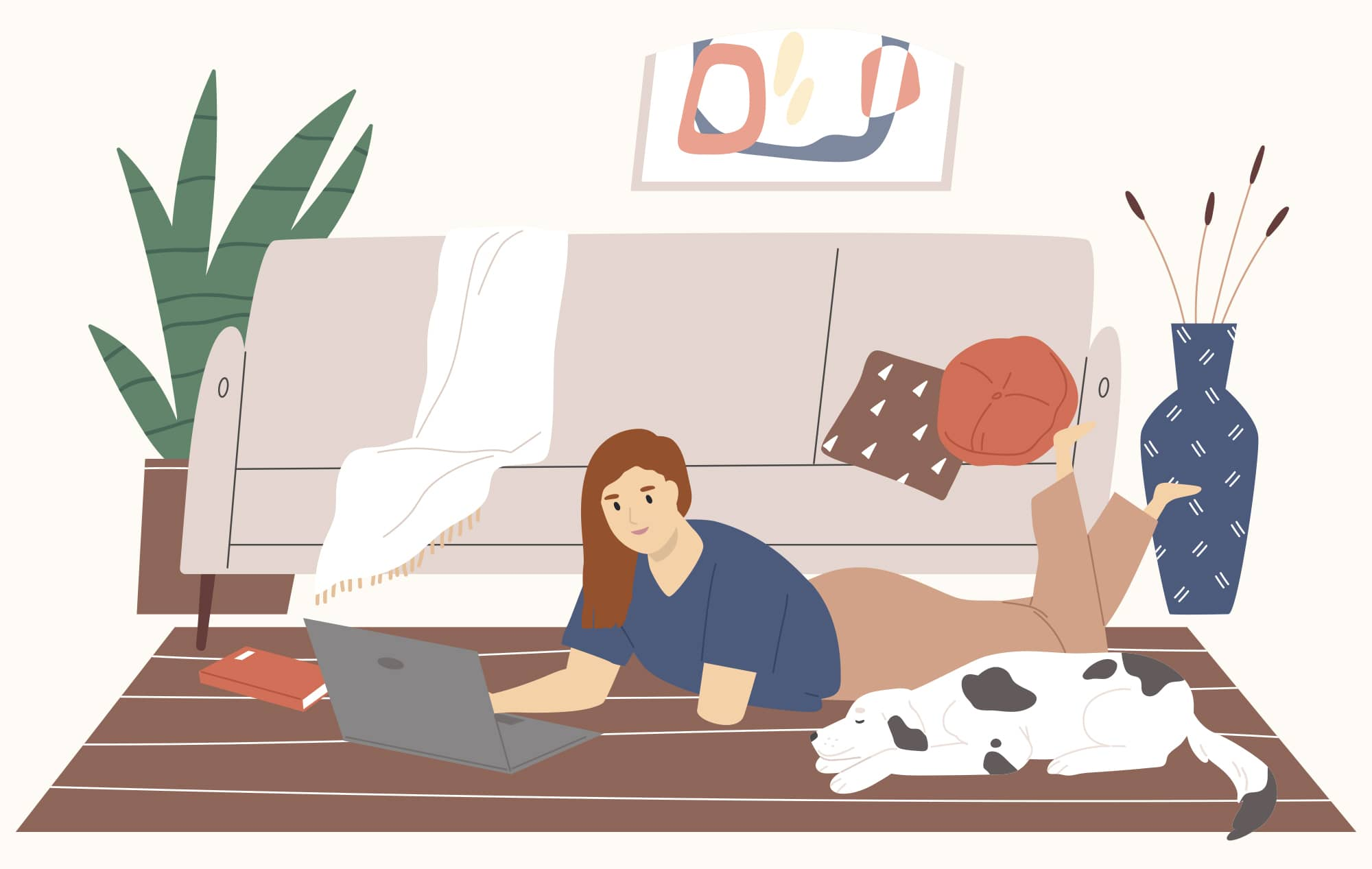 Redheaded woman with a limb difference lays on the floor working on her laptop while a dog sleeps next to her.